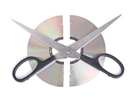 Broken CD disc with scissors isolated on white background photo