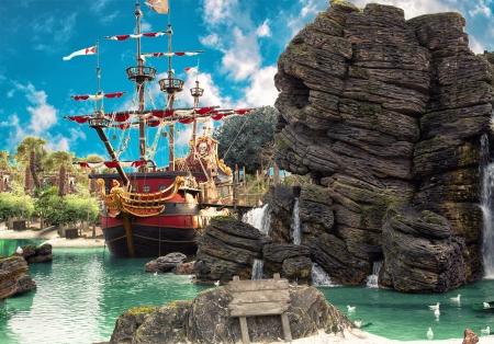 isla del tesoro: Barco pirata en el remanso de la isla tropical de piratas, con gran roca en forma de calavera cerca de él