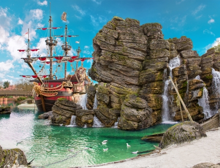 Pirate ship in the backwater of tropical pirate island, with big rock in form of skull near it