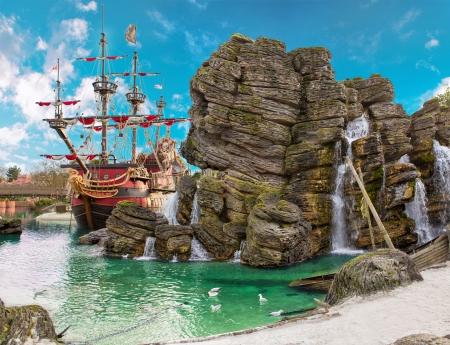 Piratenschip in de uithoek van tropische piraat eiland, met grote rots in de vorm van de schedel in de buurt is Stockfoto