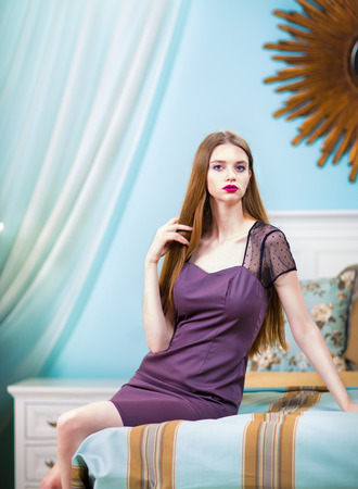sexy girl posing: Beautiful woman in purple dress in luxury bedroom interior. Stock Photo