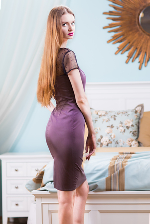 luxury bedroom: Beautiful woman in purple dress in luxury bedroom interior. Stock Photo