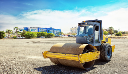 roller compactor: Roller compactor machine flattens the asphalt, with landscape behind it Stock Photo