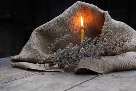 dry grass: Burning candle, dry grass on a background of burlap and wooden planks Stock Photo