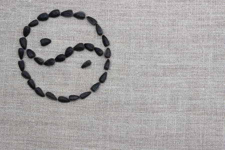 sunflower seeds: Yin yang symbol inlaid with sunflower seeds on a linen cloth