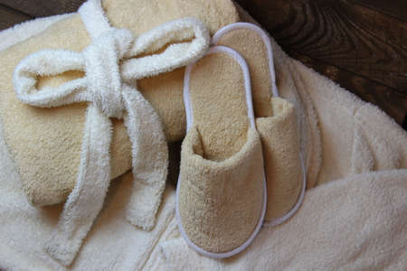 bath gown: Terry cloth towel and bath slippers lying on a dressing gown.