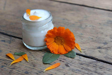 liniment: Face cream in a glass jar with a flower calendula on a wooden board.Cosmetics.
