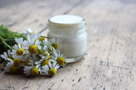 liniment: Face cream in a glass jar with flowers of chamomile on a wooden board.Cosmetics.