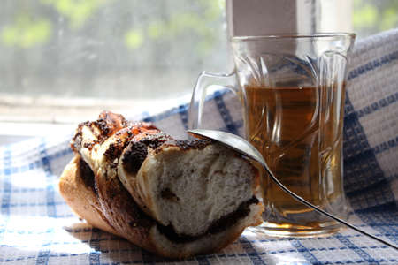 poppy seeds: Glass of tea and a bun with poppy seeds