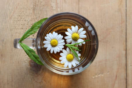 chamomile tea: Glass of chamomile tea on wooden boards Stock Photo