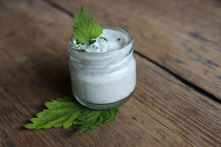 liniment: Organic face cream with leaf of nettle on wooden boards