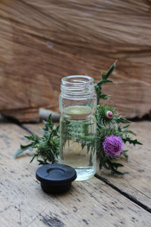 noxious: Glass jar with thistle oil on the background of wooden boards