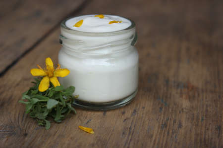 liniment: Organic face cream with flower hypericum on wooden boards