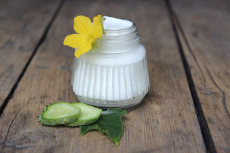 liniment: Organic face cream cucumber with flower on wooden boards