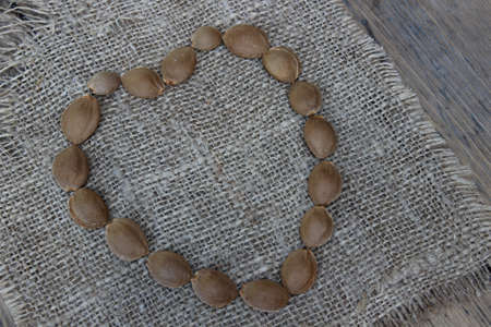 sacking: Heart laid out from apricot seeds on sacking Stock Photo