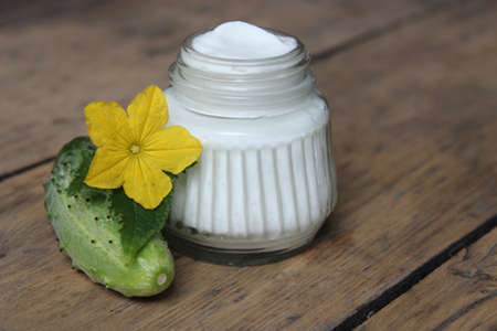 Organic face cream cucumber with flower on wooden boards