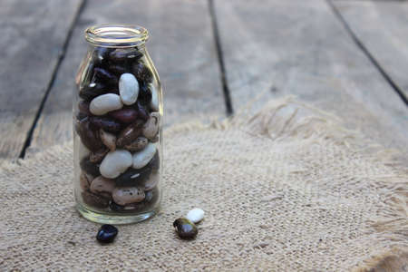 soy bean: Colorful beans in bottle on linen cloth Stock Photo