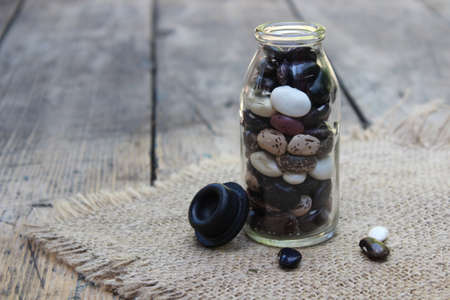 Colorful beans in bottle on linen cloth Stock Photo