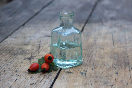 Glass bottle with oil and rosehip berries