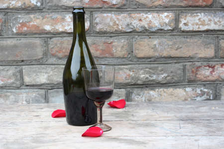 Bottle of wine and glass on the background of brick wall