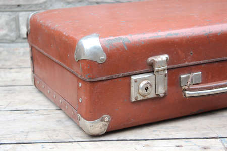 Old brown suitcase on the background of boards and walls