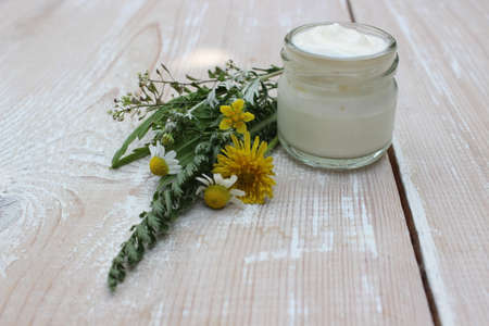 Cosmetic cream with chamomile flowers Imagens