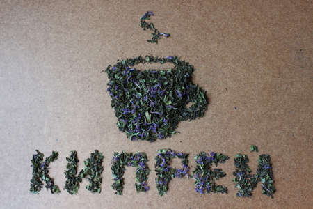 Dry Russian Ivan-tea laid out in the form of an inscription tea with a cup