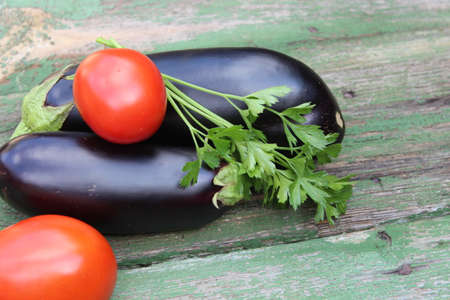 Eggplant fruits and tomatoes on wooden boards. Agriculture. Harvest
