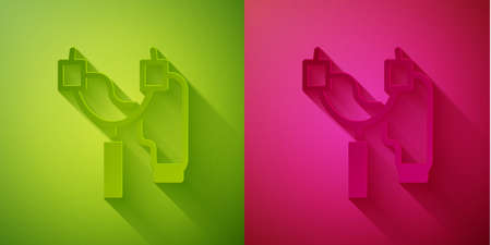 Paper cut Slingshot icon isolated on green and pink background. Paper art style. Vector
