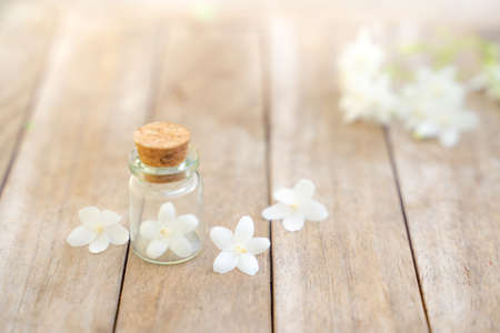Glass bottles have small flowers on the wooden floor.
