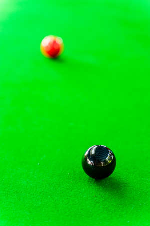 Black and red snooker balls on the snooker table