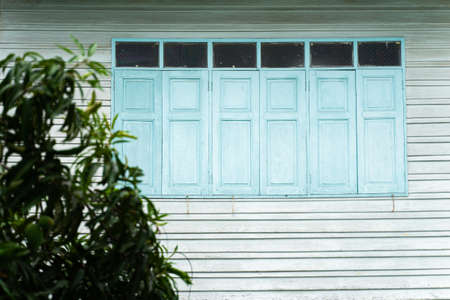 Blue house windows, old wooden houses with trees in front Imagens