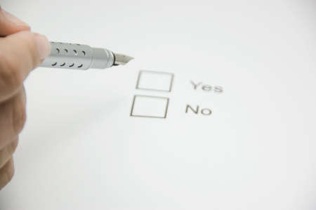 pen in a male hand hovering above selection boxes marked yes and no