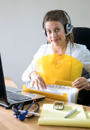 help desk woman sitting behind her desk at the office looking browsing through folder while talking to client online.