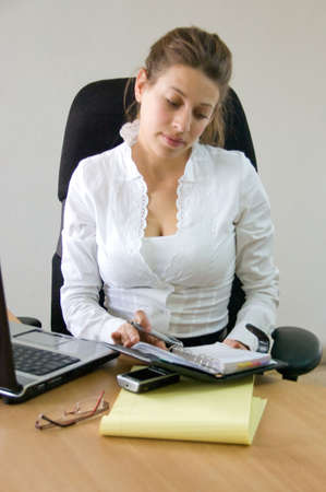 business woman behind her desk at the office browsing through her agenda
