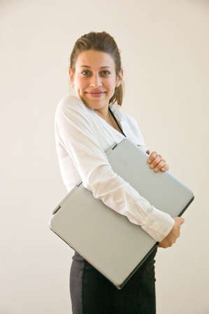 Business woman holding laptop at office looking into the lens