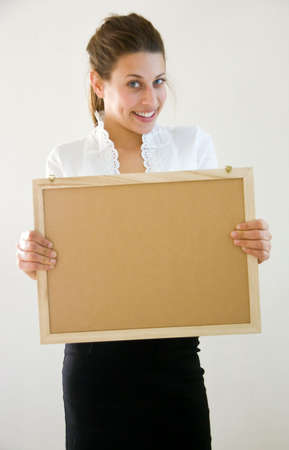 Business woman holding blanco sign at office looking into the lens