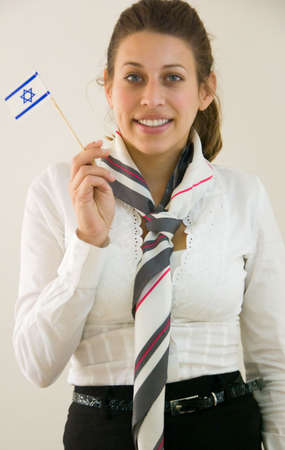 Friendly stewardess is holding a little Israeli flag promoting her country. Stock Photo