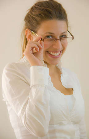 bussiness woman holding glasses in the office looking into the lens