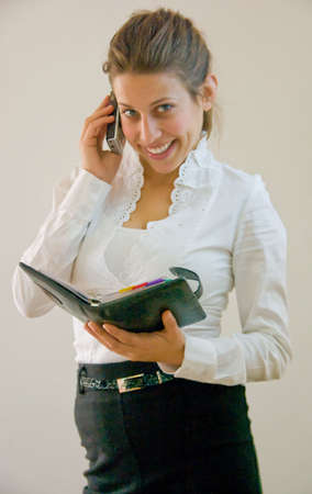 help desk woman at the office browsing through agenda while talking to client on the phone.