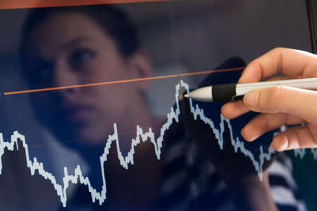 reflection of woman on lcd screen pointing at touchscreen to a stockmarket result