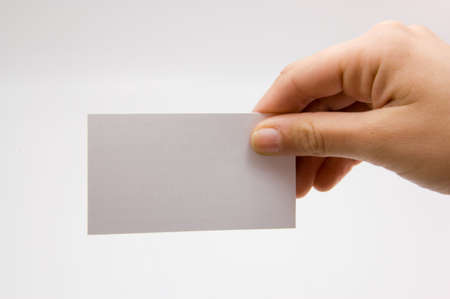 female hand holding blank business card on a white background.