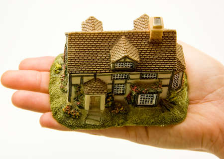 Female hand on white background holding minature house in her palm