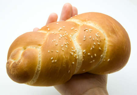Shabbat bread held by a female hand on a white background Stock Photo
