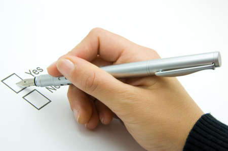 decission: pen in a male hand hovering above selection boxes marked yes and no