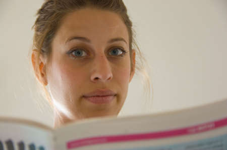 young woman with blue eyes is looking over the edge of her newspaper. Stock Photo - 4409330