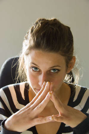 woman looking in lens of the camera with hands fold infront of her face Stock Photo