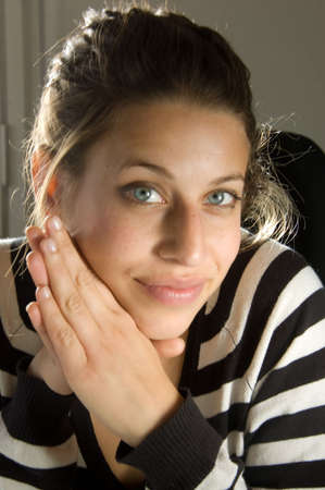 woman looking in lens of the camera with hands fold next to her face