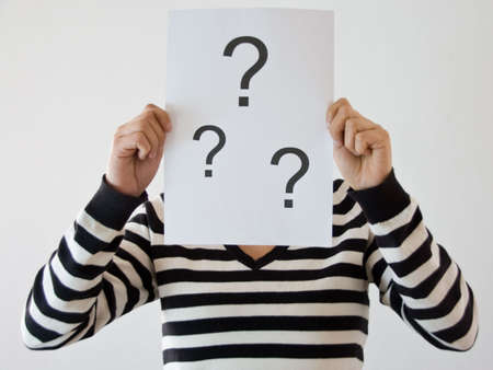 woman with question marks infront of her face in striped shirt Stock Photo