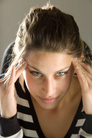 woman massaging her head because of a bad headache while looking in the lens
